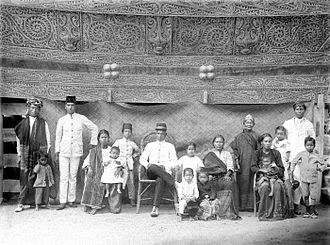 Toba Batak people - Toba head with his family in their home with beautifully carved head of Toba family (adathuis) Tapanoeli, North Sumatra, circa 1900.