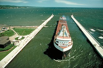 Duluth Ship Canal - Unidentified laker entering the Duluth Ship Canal from the lake. The two entrance lights can be seen at the end of the piers, while the museum building is at the extreme left.