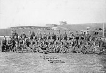 A group of soldiers standing, kneeling or lying down in a group photograph