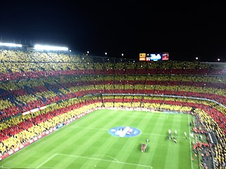 El Clásico - Camp Nou. The home fans of FC Barcelona are creating a mosaic of the Catalan flag before El Clasico. The top right corner of the club's crest also features a Catalan flag.