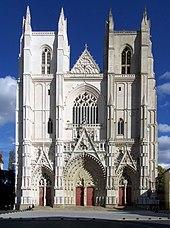 Façade: deux tours carrées encadrent la nef, bâtiment de style gothique en tuffeau blanc