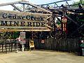 Cedar Point Cedar Creek Mine Ride trains in motion near sign (1867).jpg