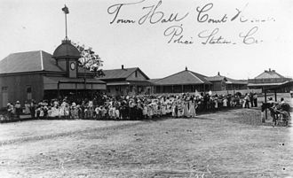 Town of Croydon - A large crowd is gathered in the main street of Croydon, circa 1901, possibly to celebrate Federation. Buildings include the Town Hall, Court House and Police Station. The Queensland Mining building is at the bottom of the street.