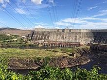 bir nehir, yüksek eğimli bir beton duvarın tabanındaki dikdörtgen açıklıklardan, nehrin üzerinde elektrik kabloları ile düzgün bir şekilde akar.