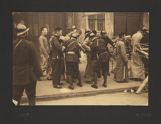 Victor Sassoon - Chinese Civilians with Japanese Soldiers at Checkpoint (1937), a photograph by Victor Sassoon taken in Shanghai during the Second Sino-Japanese War