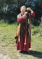 Costumed early middle age woman spinning drop spindle.jpg
