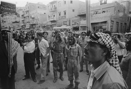 Crowd of men and soldiers in downtown Amman, Jordan, watching a news report about the deposition, 14 July 1958 Crowds in downtown Amman watching a news report about King Faisal's deposition 14 July 1958.png