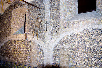 Hanging on a wall built from human bones is th...