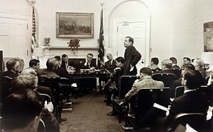 William Conrad Gibbons - Dr. William Conrad Gibbons (standing), Professional Staff Member of the Democratic Policy Committee and Assistant to the Majority Leader of the Senate, with Senator Lyndon B. Johnson seated in the background