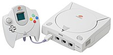 A Dreamcast. It is a white system with a disk drive on top and a controller with a display screen attached