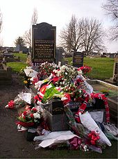 A gravestone almost entirely covered in floral tributes