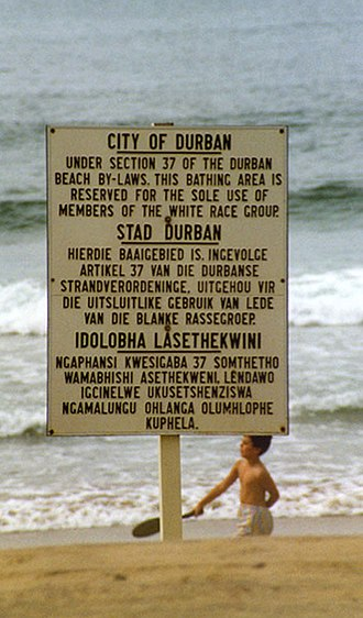 Sign - A signboard on a beach in Durban in apartheid-era South Africa indicates a racially segregated beach.