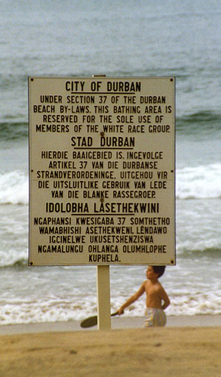 "In Apartheid South Africa, a trilingual sign in English, Afrikaans and Zulu enforces the racist segregation of a Natal beach as exclusively ""for the sole use of members of the white race group"" DurbanSign1989.jpg"
