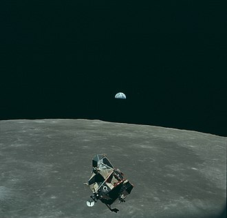 Apollo Lunar Module - Eagle, the lunar module ascent stage of Apollo 11, in orbit above the Moon. Earth is visible in the distance.