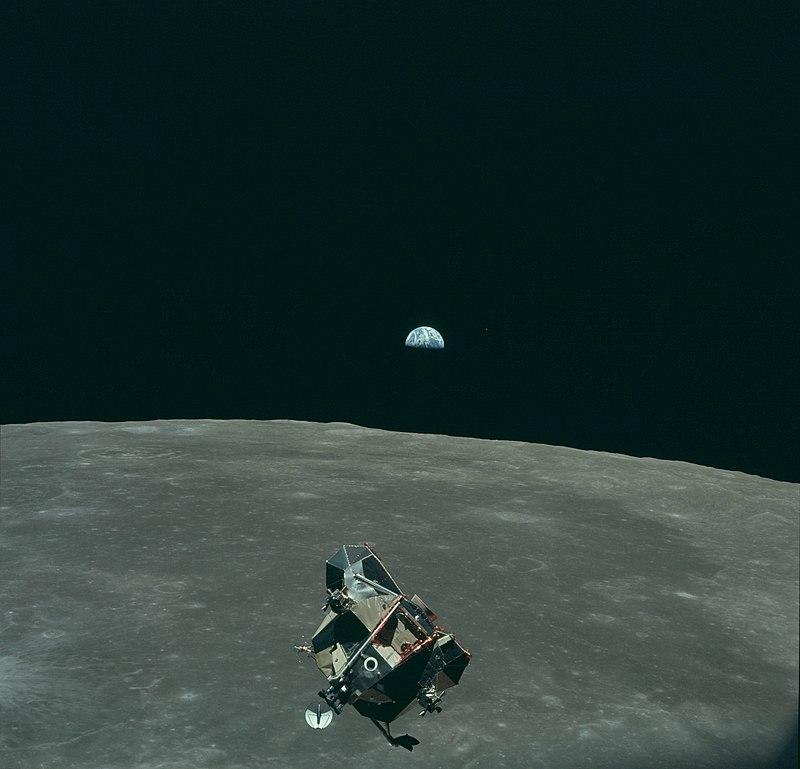 Le module lunaire d'Apollo 11, le 21 juillet 1969, de retour de l'exploration lunaire, avant l'arrimage, avec la Terre en arrière-plan. La planète Mars est également visible sur la photographie (point rouge à droite de la Terre).  (définition réelle 4170×4007)