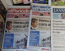 two stacks of El Periódico newspapers, one in Spanish, one in Catalan
