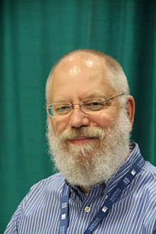 head shot of bearded poet with rimless glasses and buttoned down shirt