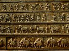 Каменное изображение четырех горизонтальных рядов: верхний ряд - танцоры, второй ряд - воины, третий - лошади и их дрессировщики, нижний ряд - слоны.