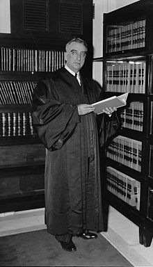 A formal portrait of an older man, sitting, in judicial robes