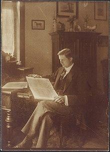 młody biały mężczyzna, gładko ogolony, z gęstą czupryną ciemnych włosów, schludnie przystrzyżony, siedzący przy biurku i patrzący na nuty