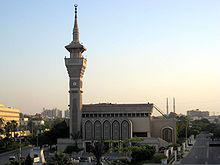The front side of a mosque with only one minaret containing a clock.