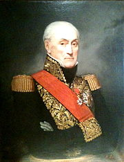 Color painting of a grim-faced older man with a receding hairline. The man, whose arms are crossed, wears a dark blue military uniform with gold epaulettes, gold braid, and a red sash across his chest.