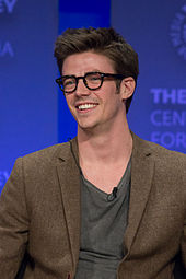 Grant Gustin, smiling and wearing morn-rimmed glasses