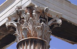 Capitel alto combinando hojas semi-naturalistas y zarcillos muy estilizados que forman volutas.