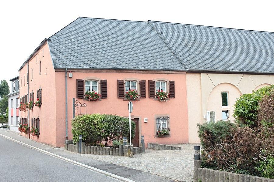 De Prommenhaff zu Grousbus, an der Baaschtnecher Strooss Nr 5; zënter dem 26. Januar 1988 op der Lëscht vum Zousaz-Inventaire vun den nationale Monumenter agedroen.