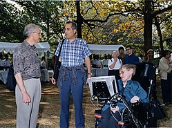 Hawking outside, in his wheelchair, talking to David Gross and Edward Witten