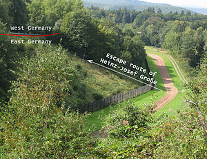 "A lush, green, wooded landscape through which the border line about 10 metres (32 ft) wide, cleared and grassed with a narrow dirt strip in the middle, runs from bottom-left across the image, turning slightly to run directly away from the viewer into the distance. To the right is the outer fence and a steep incline leading up to the near-side fence of a West German road. A schematic arrow, marked ""Escape route of Heinz-Josef Großze"", points to a memorial cross at the point of the shooting, half way up the incline."