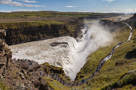 View of the 32 m (105 ft) high and 20 m (60 ft) wide crevice of the Gullfoss waterfall located in Suðurland, Iceland. The crevice extends perpendicular to the flow of the river and is 2.5 km long. The average amount of water running over this waterfall is 140 m3/s in the summertime, but up to 2000 m3/s have been measured. Together with Þingvellir and the geysers of Haukadalur, Gullfoss forms the Golden Circle, the most popular touristic attraction in Iceland.