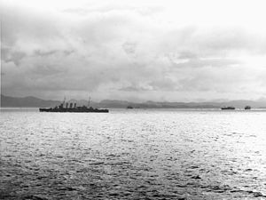 HMAS Canberra (D33) - Canberra under way off Tulagi during the landings on 7–8 August 1942. Three transports are among the ships visible in the distance, with Tulagi and the Nggela Islands beyond.