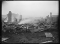 Houses destroyed by fire in Petone, with corrugated iron lying on the ground, several chimneys standing, and with the fire still smoking. ATLIB 272770.png