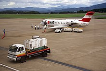 A Bombardier CRJ-200 aircraft parked on the tarmac with passengers approaching the aircraft for boarding. There is also a baggage trolley and two carts next to the aircraft. There is an auxiliary power unit in the foreground and a mountain view in the background
