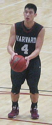 Lin wearing a crimson colored Harvard basketball jersey