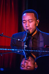 John Legend playing a piano