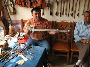 Rawap - A man playing a rawap in a shop in Kashgar, Xinjiang, China