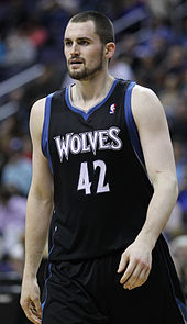 Kevin Love, bearded, in a black Timberwolves uniform with blue and white trim