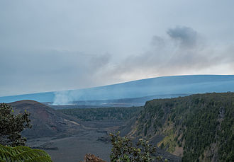 Kīlauea - View from the edge of Kilauea Iki: across the caldera, Halemaumau Crater lies smoking on the left, and Mauna Loa towers above in the background