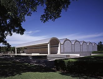 Kimbell Art Museum - The south wing of the museum showing a portico and five vaulted galleries. The tree-lined entry courtyard is at the far left.