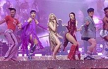 Minogue con un traje dorado cantando y bailando en un escenario acompañado por cinco bailarines con coloridos trajes