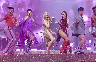 "Spinning Around - Minogue, dressed in a golden dress and flanked by dancers, performs ""Spinning Around"" during the Golden Tour (2018)."