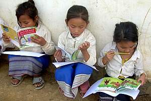 English: Three Lao girls sit outside their sch...