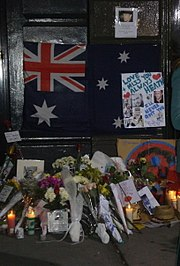 "Dark doorway and doorstep with section of footpath. On the lower part of the dark door is a partly obscured Australian flag with dark blue background; red and white crosses on top left, large white star underneath and three white stars at the right with others obscured. Obscuring the right side of the flag is a white sheet with light blue writing, ""Love + Miss You Always Heath"" with two red hearts nearby, other writing includes ""I'll never quit you"" in darker blue, more writing is indistinct. This sheet also has six photos of a man. Above the flag, on the door is a smaller sheet with a photo of a man and indistinct writing below. On the doorstep and section of footpath are some 14 groups of flowers wrapped in plastic or paper, together with nine or so cards, five or six lit candles, and more photos. On the right side is a straw hat."