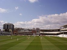 A view of a cricket ground with blue sky and some clouds, the stands surrounding the pitch are mainly unoccupied, to the left in the background is a large building