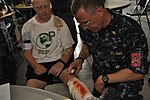 Lt. Cmdr. Tim Murphy sprays fake blood on Pennsylvania CAP cadet.JPG