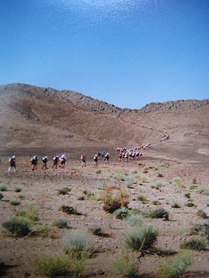 Marathon des Sables - Racers winding their way up a large ridge.