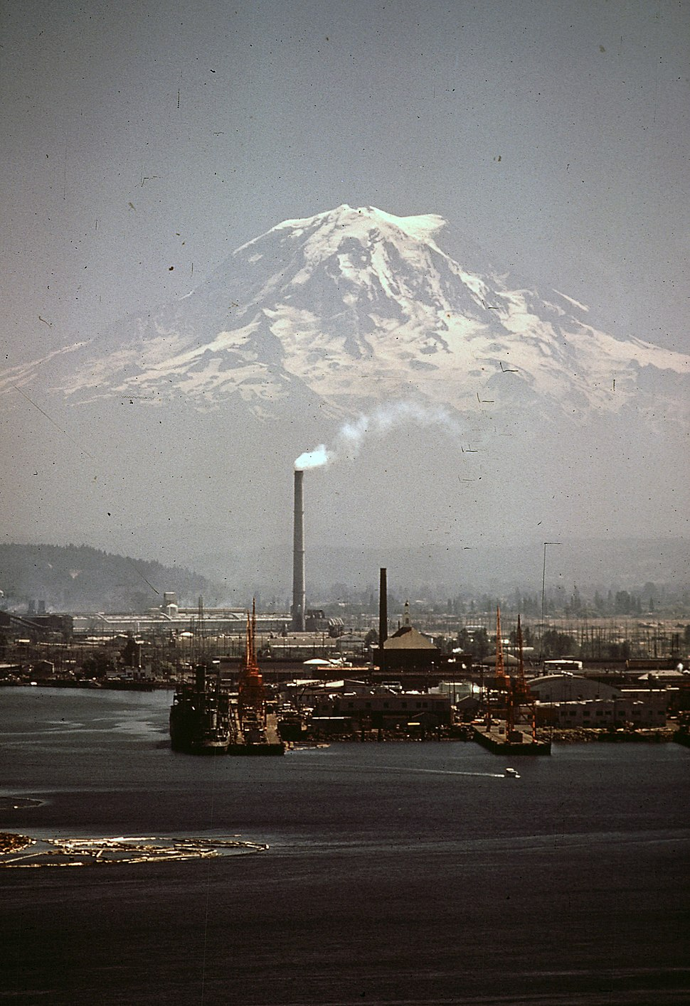MT. RAINIER, WITH PORT OF TACOMA IN FOREGROUND. STACK BELCHING SMOKE MARKS THE KAISER ALUMINUM PLANT - NARA - 545243