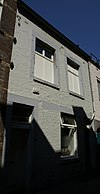 foto van Huis met lijstgevel, met hardstenen kozijnen waaruit de kruisen, resp. middenstijlen verdwenen zijn.